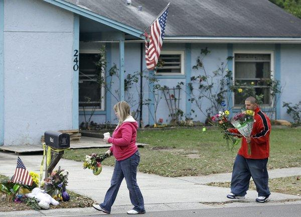 Jeremy Bush, right, carries flowers to a makeshift memorial Sunday outside a home where a sinkhole opened up underneath a bedroom late Thursday evening and swallowed Jeremy's brother, Jeffrey, in Seffner, Fla. The home is set to be demolished Sunday.