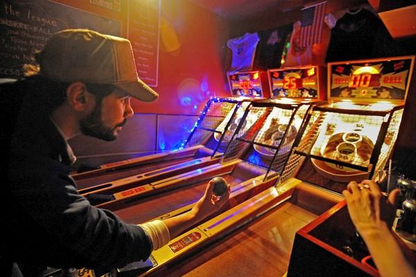 Eric Pavony, owner of the Full Circle Bar in Brooklyn, N.Y., rolls a game.