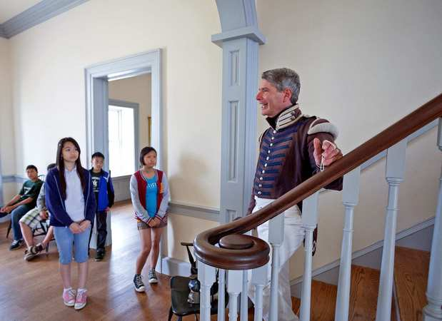 A tour guide takes students through the commander's house.