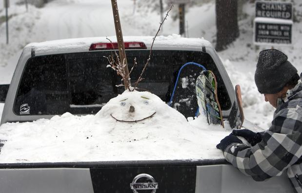 Sebastian Perez of Rancho Cucamonga puts the finishing touches on a snowman face in the back of his pickup truck.