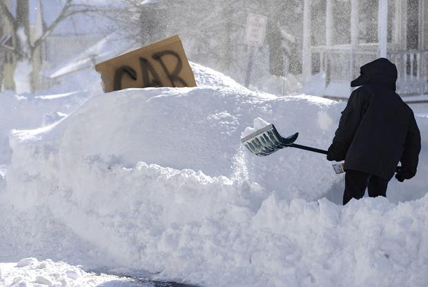 A boy digs around a car marked with a sign on a street in Windsor Locks, Conn. A major blizzard packing hurricane-force wind gusts swept through the Northeast overnight