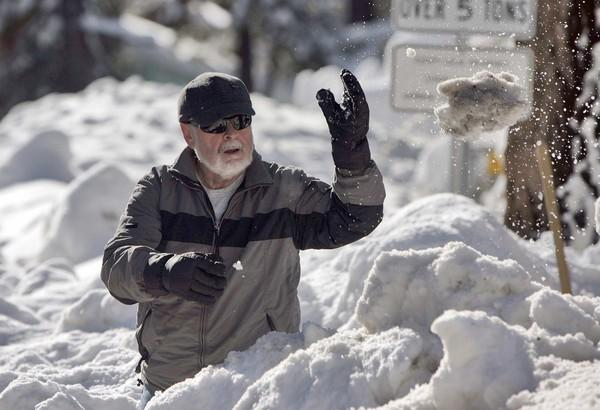 Keith Perkins clears waist-deep snow from his driveway in Wrightwood.