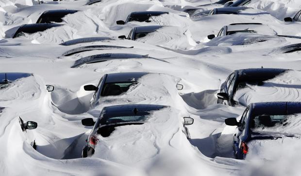 Snow begins to melt on cars parked at a dealership after a winter storm in Hartford, Conn.