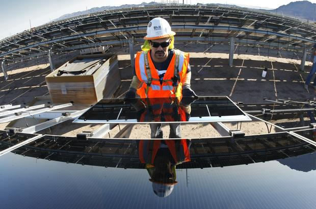 Adrian Pacheco installs a photovoltaic panel at the Tenaska Imperial Solar Energy South project in the Imperial Valley west of El Centro, Calif.
