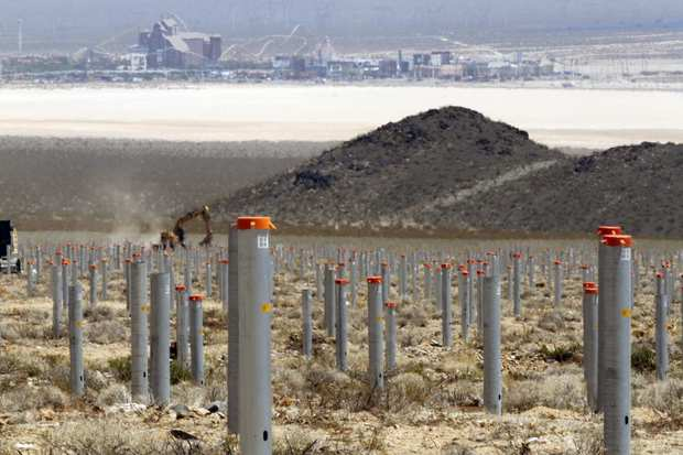 The casinos and shopping center at the Nevada state line provide the background for the posts that will support the mirror structures, called heliostats, at the solar plant.