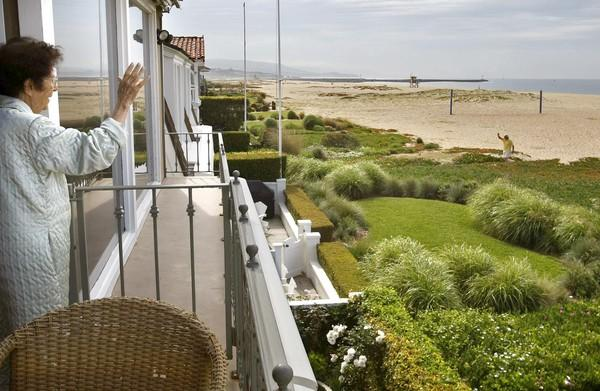 "A resident waves to a neighbor from the balcony of her beachfront home on Balboa Peninsula in Newport Beach. Recently, the California Coastal Commission sent letters to homeowners along East Oceanfront, saying that the lawns, shrubbery and flowers they installed are ""unpermitted landscaping on public beach."""