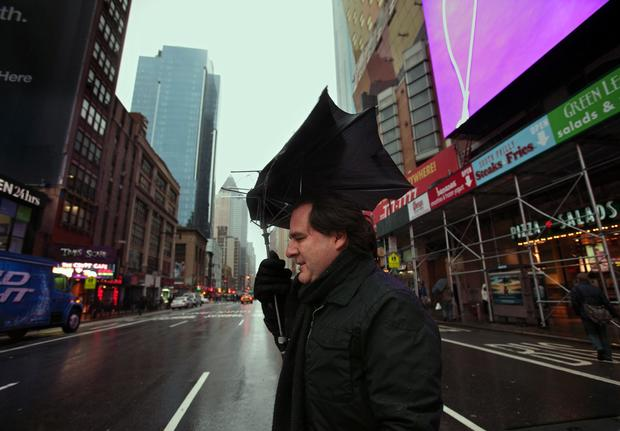 Emilio Vreca of Bethlehem, Pa., makes his way along 42nd Street in Manhattan with a broken umbrella.