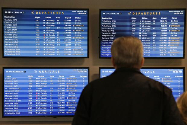 TV monitors at Logan International Airport in Boston show canceled flights. Boston and much of eastern Massachusetts were under a blizzard warning.