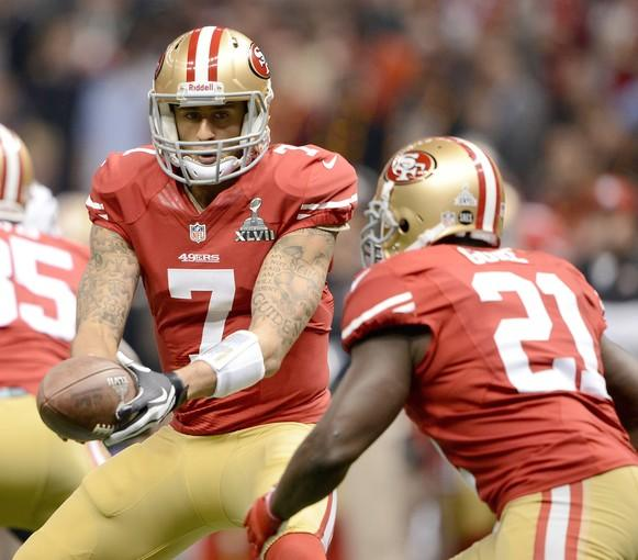 49ers quarterback Colin Kaepernick hands off to running back Frank Gore in the first quarter Sunday.