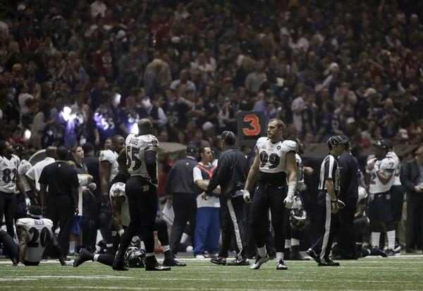 Ravens players look around after the lights went out during a power surge at the Superdome early in the third quarter Sunday.