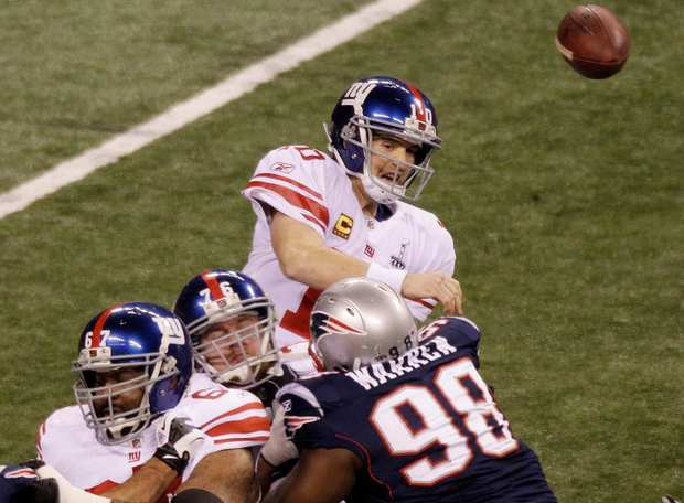 Giants quarterback Eli Manning passes over a strong Patriots rush in the first quarter of Super Bowl XLVI on Sunday.