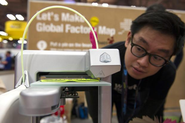 Tim Wong, co-founder of FabCafe, watches his 3-D printer make a pair of sunglasses.