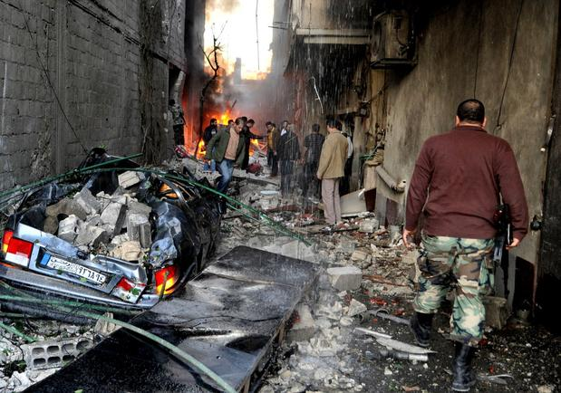 A Syrian soldier, right, and citizens gather at an alley that was destroyed by two car bombs in Jaramana neighborhood, a suburb of Damascus.