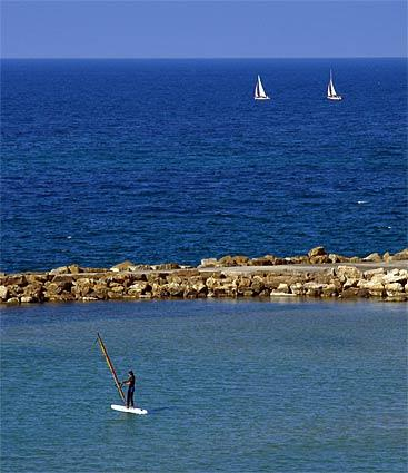 Sailors and windsurfers enjoy the waters off Tel Aviv.