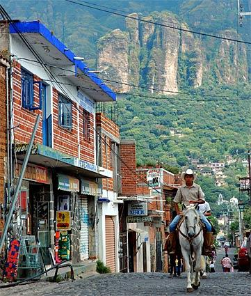 Horses occasionally join the cars and pedestrians on Tepoztlán's Avenida Tepozteco. The town's actual main drag, it leads past ancient walls, bold-colored eateries and modest lodgings before giving way to the path to the pyramid.
