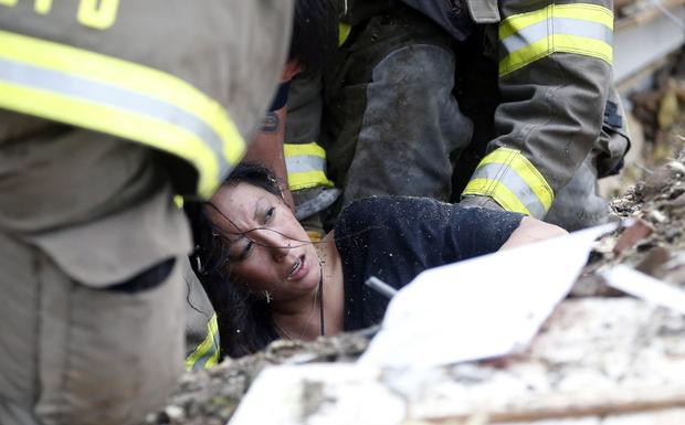 A woman is pulled out from under tornado debris at the Plaza Towers School in Moore, Okla.