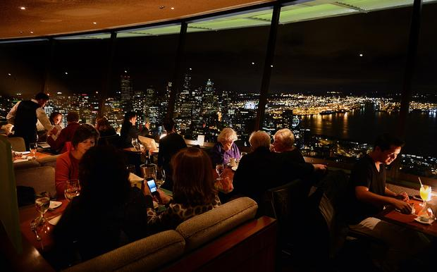 Diners enjoy food and cocktails at the SkyCity restaurant at the top of the Space Needle.