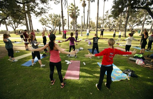 Students stretch at the conclusion of a workout in Angela Parker's Body Inspired Fitness class in Santa Monica's Palisades Park.