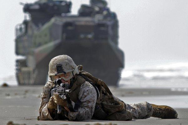 Marine Corps rifleman Marc Calo holds his position on the wet sand after coming ashore on an assault vehicle at Camp Pendleton. A dispute over the Trestles surf break has divided wave riders and Marines, two groups that had become allies.
