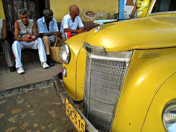 Local men sit by a colorful old roadster.