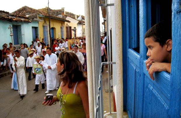 A boy watches a religious procession winds through the streets.