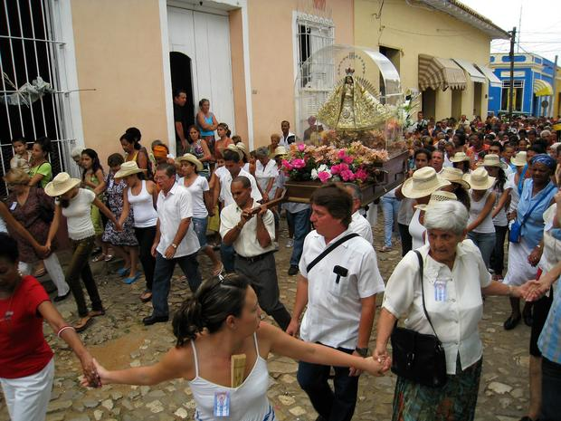 A statue of Cuba's patron saint, Our Lady of Charity, is carried toward Trinidad's cathedral in a religious procession.