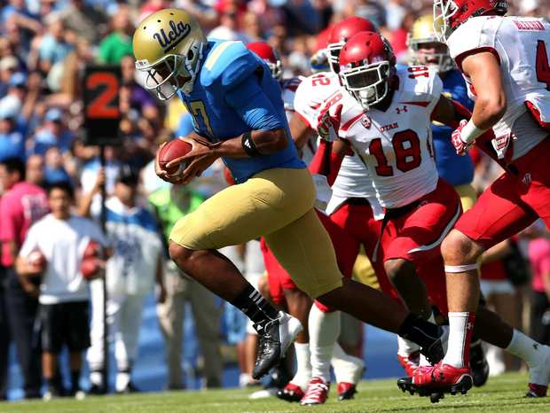 UCLA quarterback Brett Hundley bursts through the middle of the Utah line on a 12-yard touchdown run in the first half Saturday.