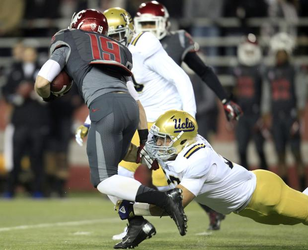 UCLA linebacker Ryan Hofmeister tackles Washington State receiver Brett Bartolone after a reception in the first quarter Saturday night.