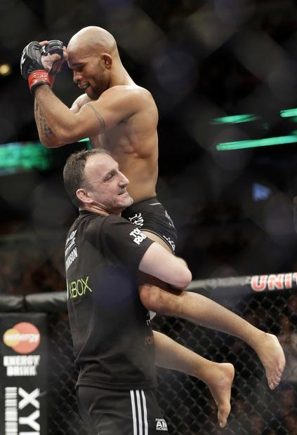 Demetrious Johnson, top, enjoys the moment after surviving a tough match with John Dodson as part of UFC Chicago on Saturday night.
