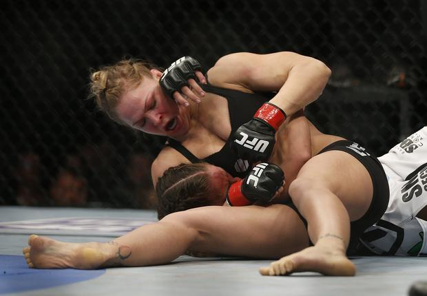 Ronda Rousey, top, controls Liz Carmouche with a headlock and punches with the other hand on her way to a first-round victory in the UFC women's bantamweight championship bout Saturday in Anaheim.