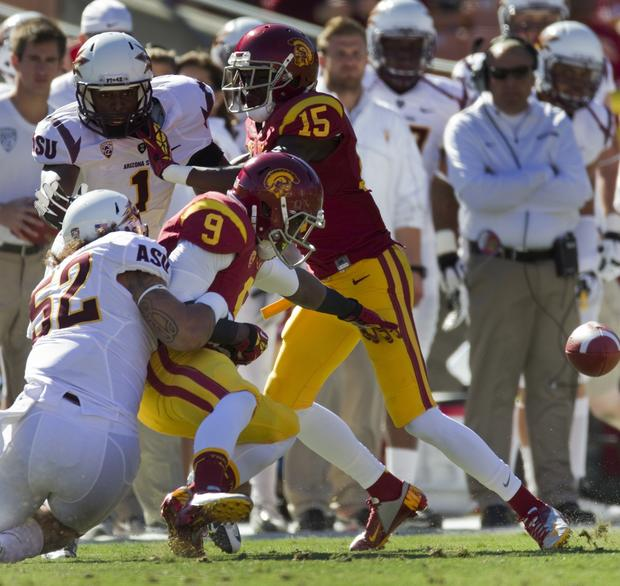 USC receiver Marqise Lee fumbles the ball after getting hit by Sun Devils linebacker Carl Bradford (52) in the first quarter Saturday at the Coliseum.