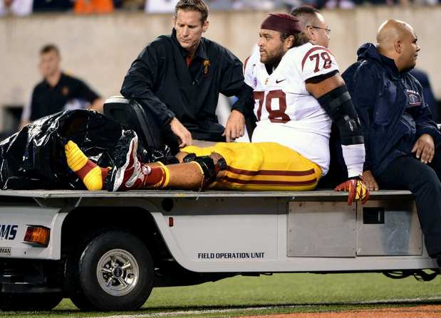 USC center Khaled Holmes is carted off the field after injuring his leg in the fourth quarter Saturday.