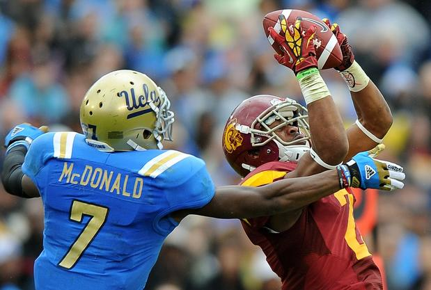 Trojans receiver Robert Woods hauls in a pass against Bruins safety Tevin McDonald during their rivalry game this fall.