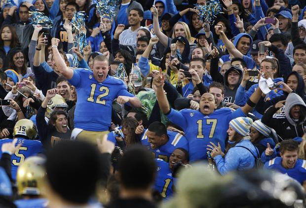 Bruins quarterbacks Richard Brehaut (12) and Brett Hundley (17) celebrate with fans after their 38-28 victory over the Trojans on Saturday at the Rose Bowl.