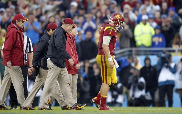 Trojans quarterback Matt Barkley leaves the field after sustaining an injury while being sacked by the Bruins in the fourth quarter Saturday.