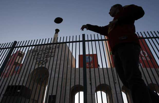 USC fan Cooper Perkins, who lives in Westwood, plays catch outside the Coliseum before the start of the game against UCLA on Saturday evening.