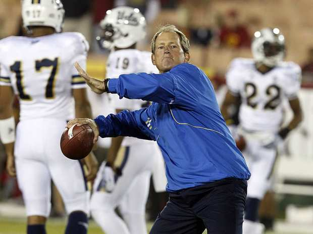 UCLA Coach Rick Neuheisel, a former Bruins quarterback, throws a pass as his players warm up for their game against USC on Saturday evening at the Coliseum.