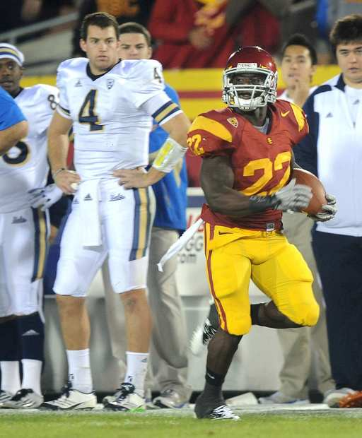 USC tailback Curtis McNeal breaks into the clear past UCLA quarterback Kevin Prince (4) and the Bruins' bench on a 72-yard scoring run in the first quarter Saturday at the Coliseum.