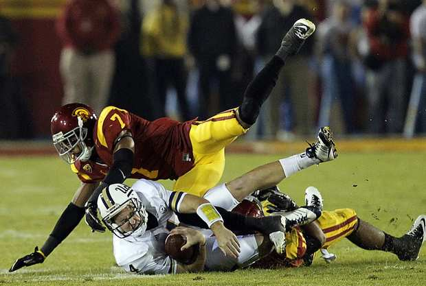 UCLA quarterback Kevin Prince is brought down by USC safety T.J. McDonald and linebacker Hayes Pullard in the first quarter Saturday night at the Coliseum.
