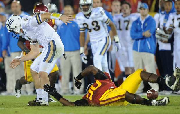 Trojans defensive tackle George Uko strips the ball from Bruins quarterback Kevin Prince in the first half Saturday night at the Coliseum. UCLA kept control of the ball when it went out of bounds.