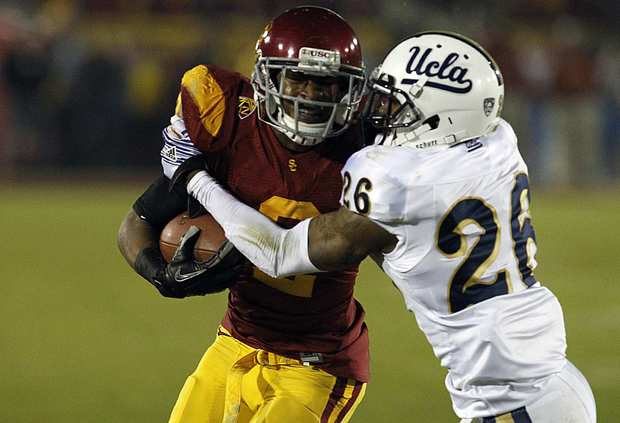 Bruins defensive back Andrew Abbott tries to bring down Trojans receiver Robert Woods in the second quarter Saturday night at the Coliseum.