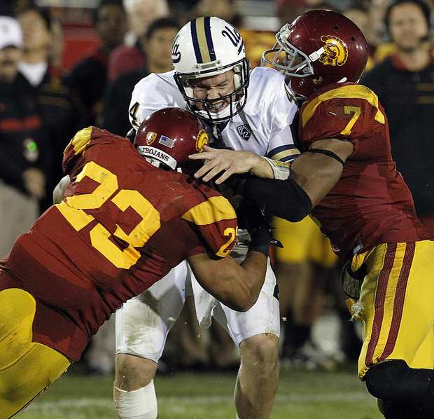 Bruins quarterback Kevin Prince is sandwiched by USC defensive end Shane Horton (23) and safety T.J. McDonald in the fourth quarter Saturday night at the Coliseum.