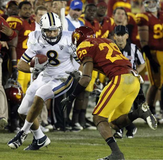 UCLA tight end Joseph Fauria tries to elude USC safety Jawanza Starling in the fourth quarter Saturday night at the Coliseum.