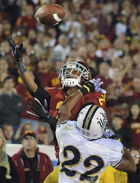 USC receiver Robert Woods goes up for a touchdown catch over Bruins defensive back Sheldon Price in the third quarter Saturday night at the Coliseum.