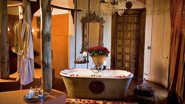The soaring bathrooms have free-standing tubs with hand-beaded chandeliers above, gilt mirrors, buckets of fresh roses, floor-to-thatched-roof silk curtains and stupendous views of the crater and beyond. It is not uncommon to be steeping in the tub and have a zebra or a wildebeest saunter past your window.