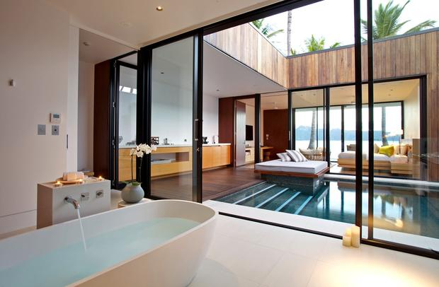 The resort's beach villas feature free-standing bathtubs, views through glass walls to the ocean, and a private heated pool.