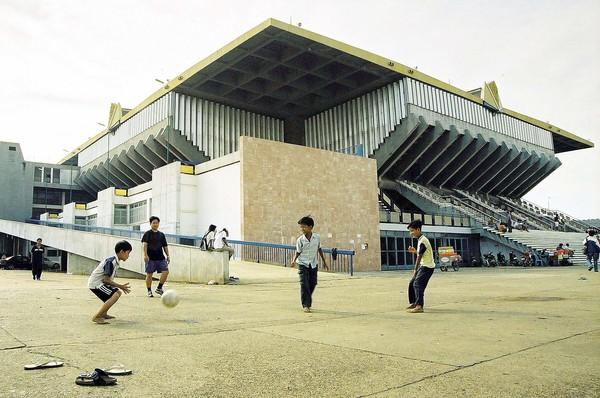 Children play soccer outside the national stadium designed by Cambodian architect Vann Molyvann in Phnom Penh. Vann Molyvann was a key creative force behind many Cambodian landmarks.