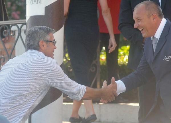 Clooney shakes hands with a member of the Cipriani hotel staff as he arrives in Venice.