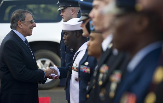 U.S. Secretary of Defense Leon Panetta greets members of a military honor guard after participating in a wreath laying ceremony at the Punchbowl Cemetery in Honolulu.