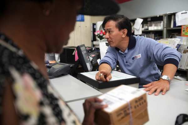 Postal worker Raymond Tran, right, 48, helps customers at the Little Saigon post office. Tran is something of an institution himself, assigned here since 1991. Nobody calls him by his last name -- it's just Raymond.